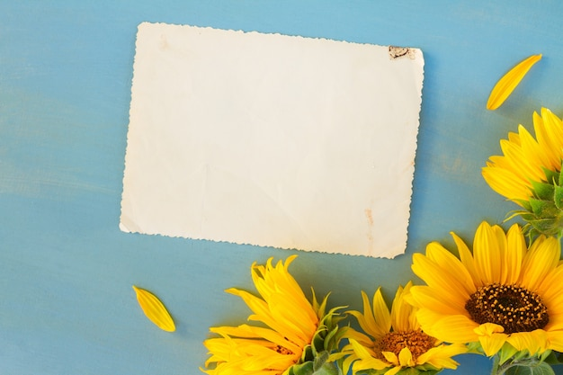 Sunflowers flowers on blue wooden background, copy space on aged paper note, top view