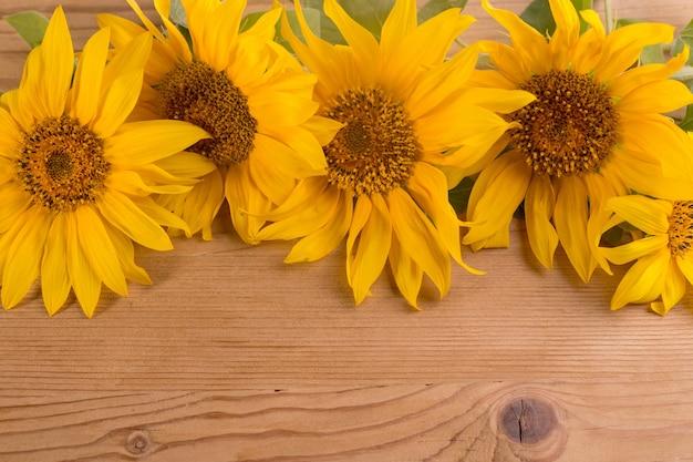 나무 소박한 테이블에 해바라기 복사 공간이 있는 밝은 노란색 여름 꽃