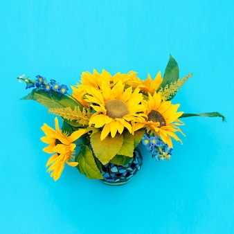 Sunflowers in a vase on a blue background. minimal art