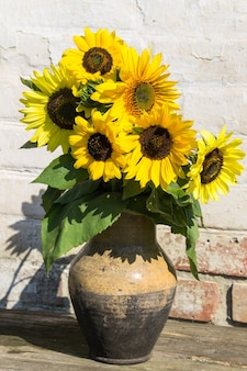 Sunflowers in vintage clay jug on rustic wooden table against white brick wall