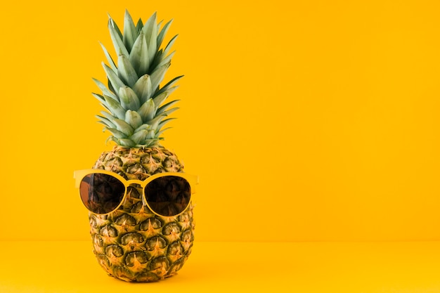 Sunglass on pineapple against yellow backdrop