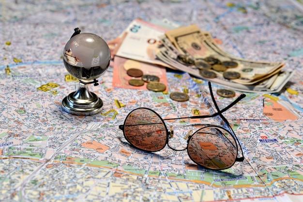 Солнцезащитные очки, стеклянный шар и деньги на фоне туристической карты. концепция туризма.