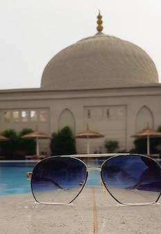 イスラム教徒のモスクを背景にしたサングラスと東部のカントリーリゾートの日陰用の傘付きのスイミングプール