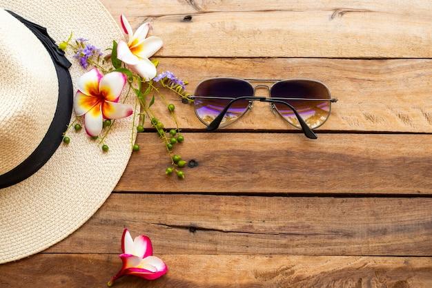 木製の背景に花とサングラスと帽子