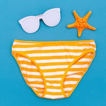 Солнцезащитные очки и трусики. отпуск. лето. минимальный пляжный стиль