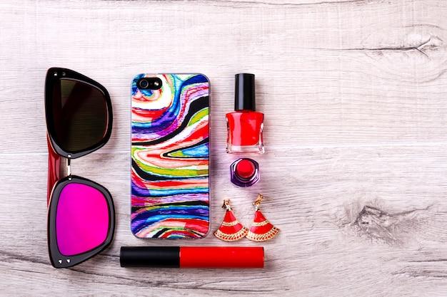 화장품 근처의 선글라스와 전화. 메이크업 및 액세서리. 나만의 스타일을 만들어보세요. 아름다움은 디테일에 있습니다.
