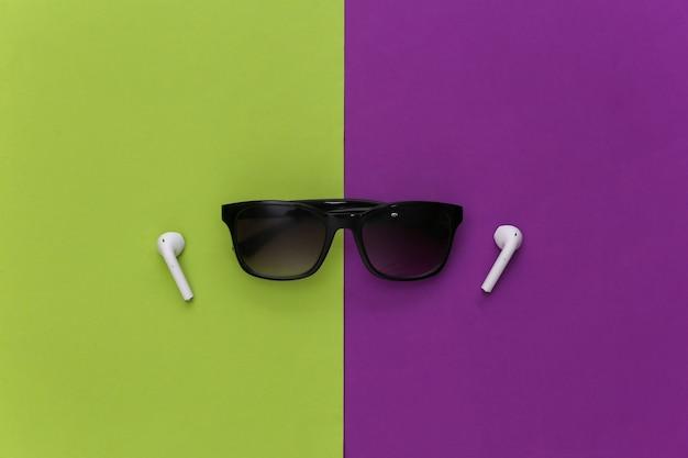 보라색-녹색 배경에 선글라스와 무선 이어폰.