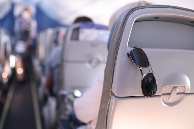 Sunglasses are placed on the passenger seat on plane