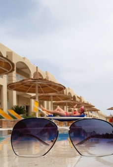 Sunglasses on the background of a sun lounger with a relaxing girl, the sky and a swimming pool with umbrellas for shade in an eastern country resort