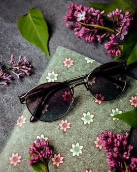 Occhiali da sole neri intorno a foglie verdi e fiori viola sulla superficie grigia
