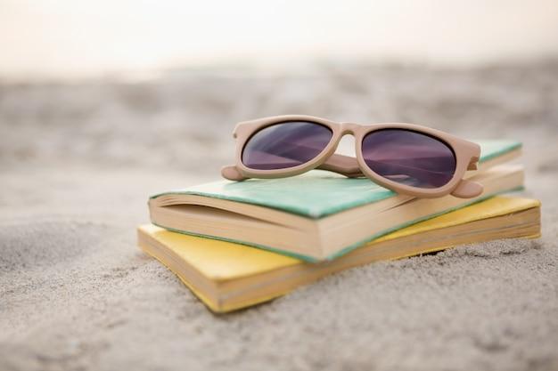 Sunglasses and books on sand Free Photo