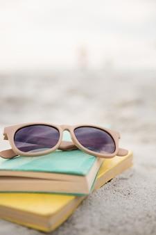 Sunglasses and books on sand