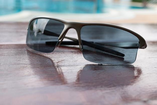 Sunglasses on brown wood table near swimming pool