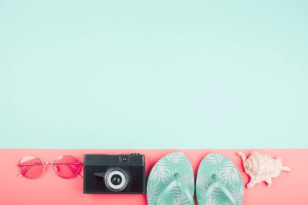 Sunglasses; camera; flip flops; conch on coral and mint background