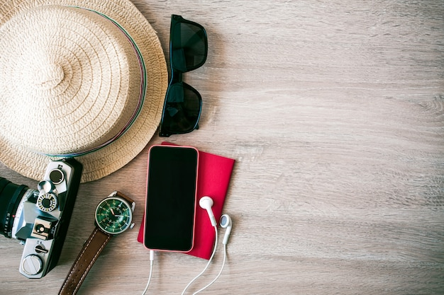 Sunglasses, camera phones, caps, passports put on wooden floor to prepare for the weekend.