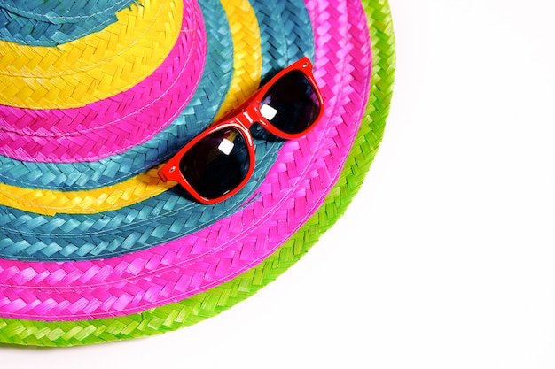 Sunglasses on a colorful straw hat on the beach. the concept of recreation and tourism. free space for text.