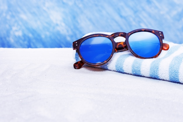 Sunglasses and cotton towel on sand beach