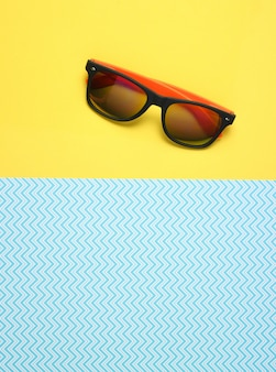 Sunglasses on creative blue yellow, summertime, top view