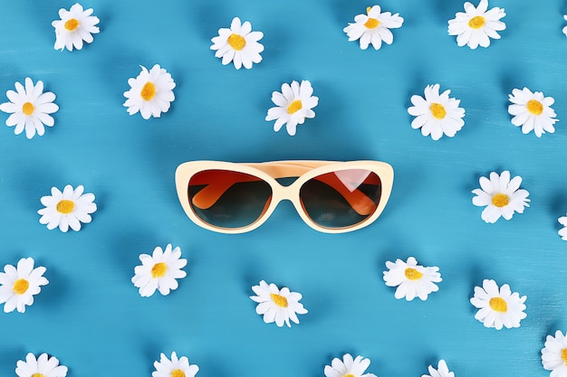 Sunglasses and daisies on blue background.