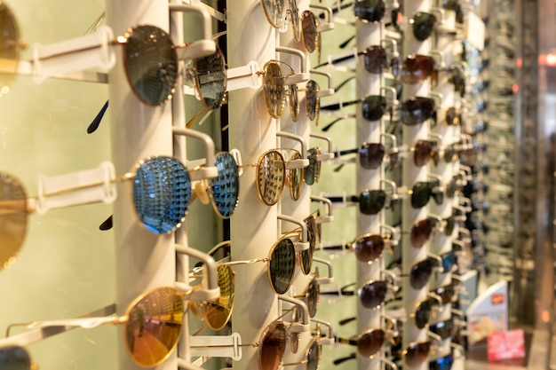 Sunglasses of different colors in a display for glasses in an optical