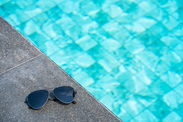 Sunglasses at the edge of the pool. vacation concept close up