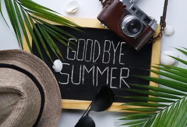 Sunglasses, fedora hat, palm leaf, camera, sea shells and blackboard
