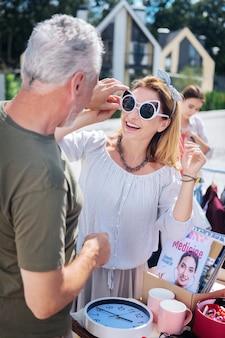 Солнцезащитные очки для женщин. бородатый седой мужчина в темной рубашке цвета хаки надевает белые солнцезащитные очки на свою красивую женщину