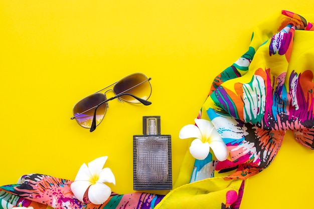 サングラス、フランジパニの花、香水、カラフルな布