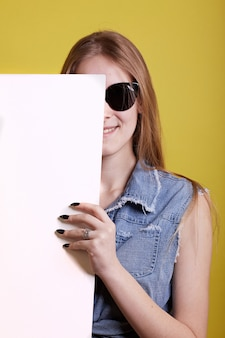 Sunglasses ginger girl hides for white painting on yellow background