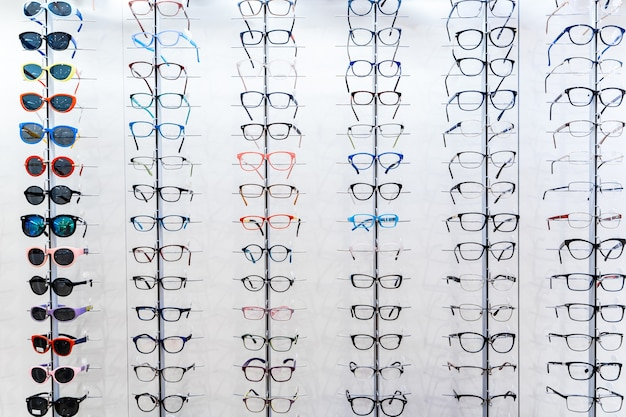 Sunglasses and glasses in the shop display shelves. stand with glasses in the store of optics.
