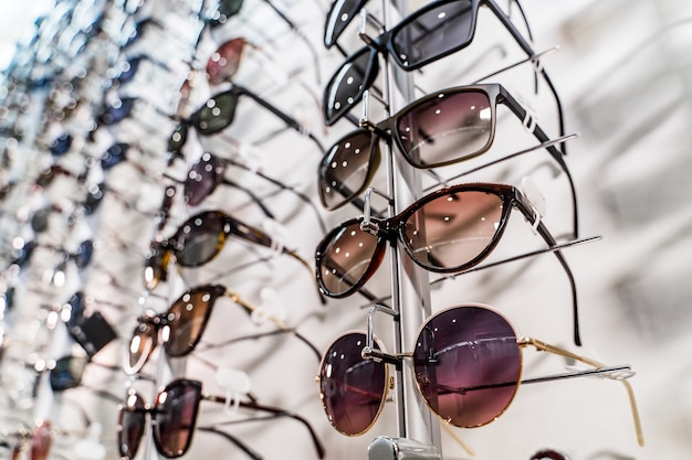 매장 진열대에 진열된 선글라스. 안경점에서 안경을 쓰고 서십시오.