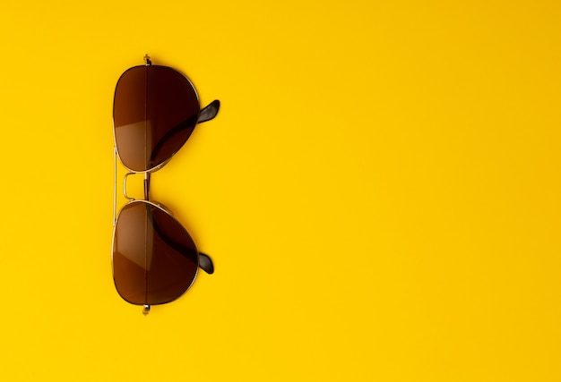 Sunglasses isolated on yellow background with copyspace.