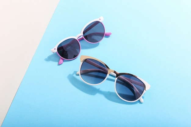 Sunglasses lie on colored casting a harsh shadow, concept art of summer and relaxation, minimalism.