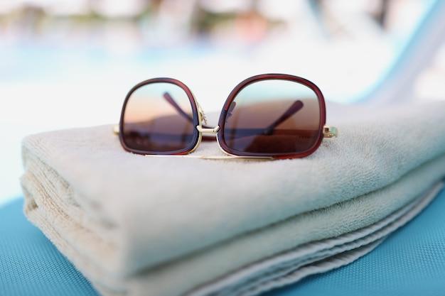 ラウンジャーのクローズアップの茶色の綿タオルの上に横たわっているサングラス