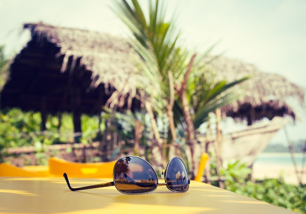 Sunglasses lying on a yellow table in a tropical beach cafe