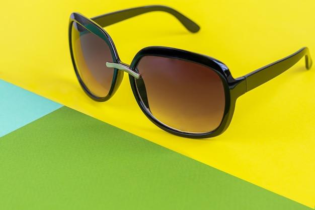 Солнцезащитные очки на цветном фоне. изолировать. здоровые глаза. скопируйте пространство.