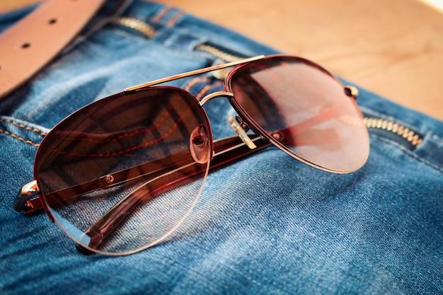 ジーンズの背景にサングラス。トーンのイメージ