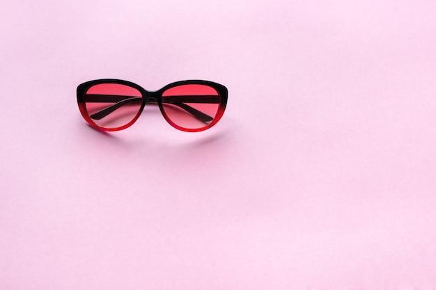 ピンクのパステルカラーの背景にサングラス。コンセプトサマー、トレンド、コピースペース。