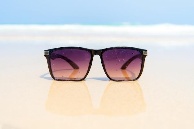 하얀 모래 해변에 선글라스입니다. 태국 시밀란 제도. 선글라스는 거울처럼 황금빛 젖은 모래에 반사