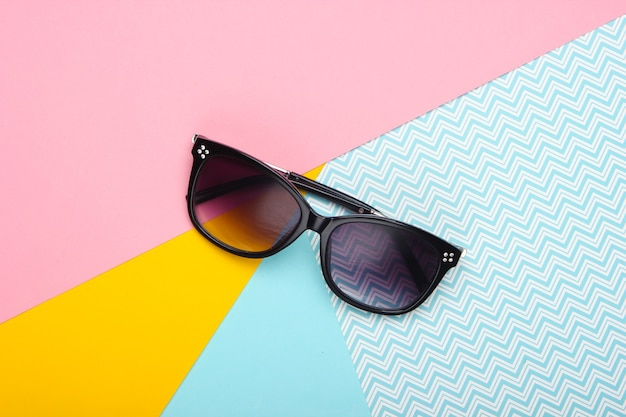 Sunglasses on a pastel colored background. top view