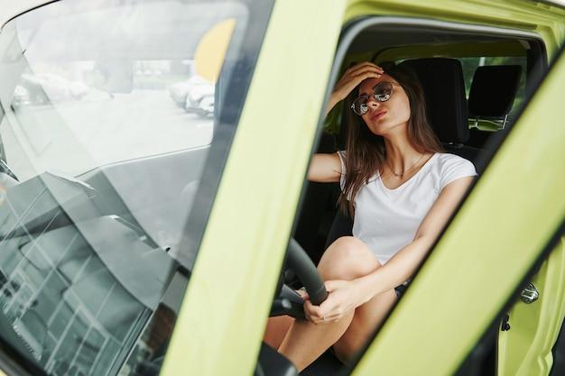 In sunglasses. pretty woman in the green modern car posing