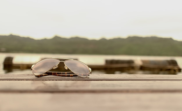 Sunglasses put on a wooden travel