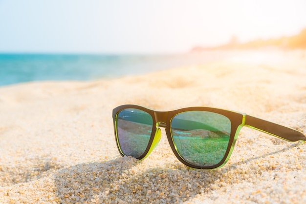 Sunglasses on the sandy coast. summer concept.