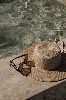 Sunglasses and straw hat on marble swimming pool side with clear blue water with waves sunlight shadow reflections