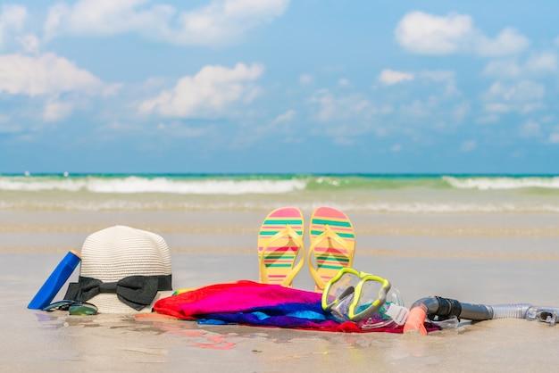 선글라스, 썬 크림 및 하얀 모래 해변에 모자