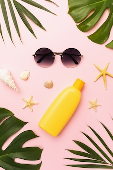 Sunglasses sunscreen seashells chico leaves and monstera leaves on a pink background