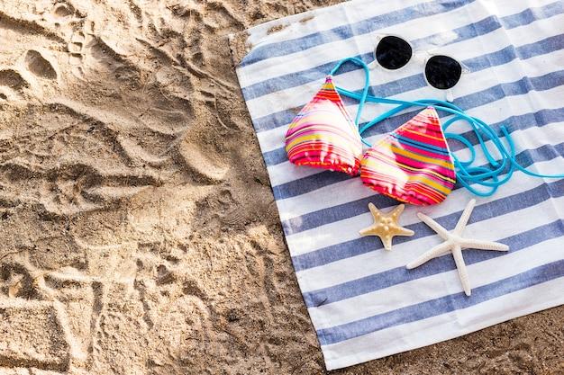 Occhiali da sole, costume da bagno e stelle marine su telo mare sulla spiaggia di sabbia