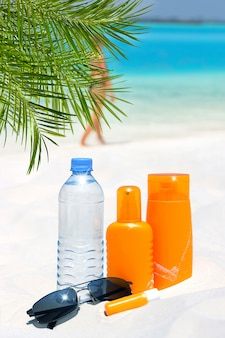 Sunglasses, water and sun protection cream on the beach