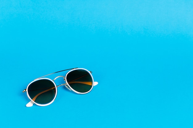 Sunglasses in a white frame isolated on a blue.