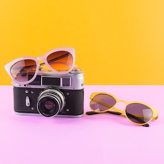 Sunglasses with camera on pink desk against yellow backdrop
